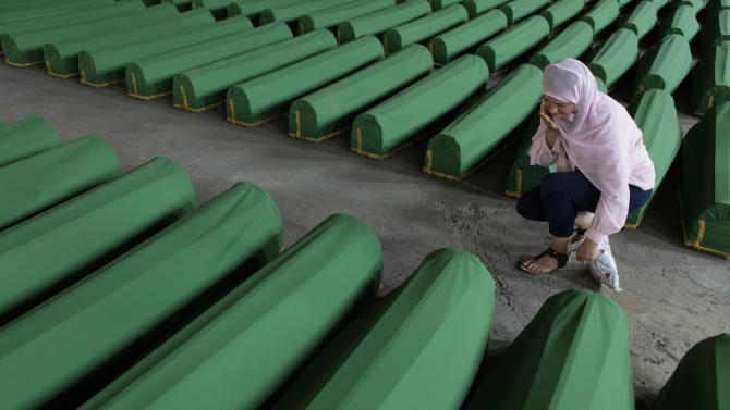 A Bosnian woman search for the body tag of her relative, among 520 newly identified Srebrenica victims, at the Potocari memorial cemetery near Srebrenica, , some 160 kilometers east of Sarajevo, Bosnia and Herzegovina, Tuesday, July 10, 2012. A burial ceremony for 520 of victims will be held on Wednesday, July 11, 2012 in Potocari, on the 17th anniversary of the Srebrenica tragedy when in 1995 Bosnian Serb forces stormed the enclave and systematically killed thousands of Bosnian Muslims.(AP Photo/Amel Emric)