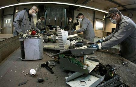 Workers sort electronic scrap on conveyor belt at a plant of Swiss recycling company Immark AG in Regensdorf