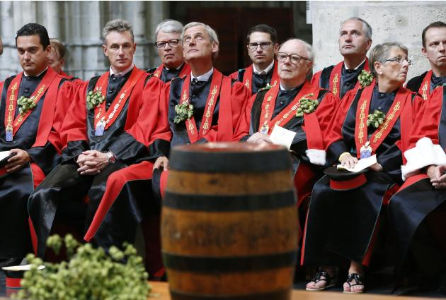Members of the Knighthood of the Brewers' Mash staff attend a mass in front of a barrel of beer at the Sint-Gudule Cathedral in Brussels
