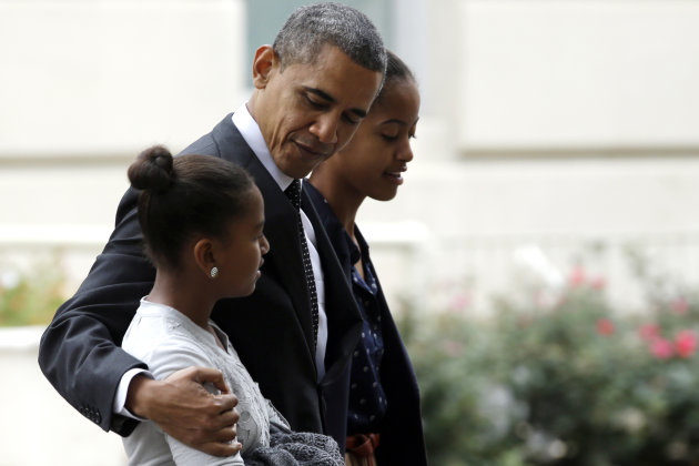 President Barack Obama hugs his daughter Sasha as he walks with Malia as they leave St. John&#39;s Episcopal Church to walk across Lafayette Park as they return to the White House in Washington, on Sunday, Oct. 28, 2012. (AP Photo/Jacquelyn Martin)