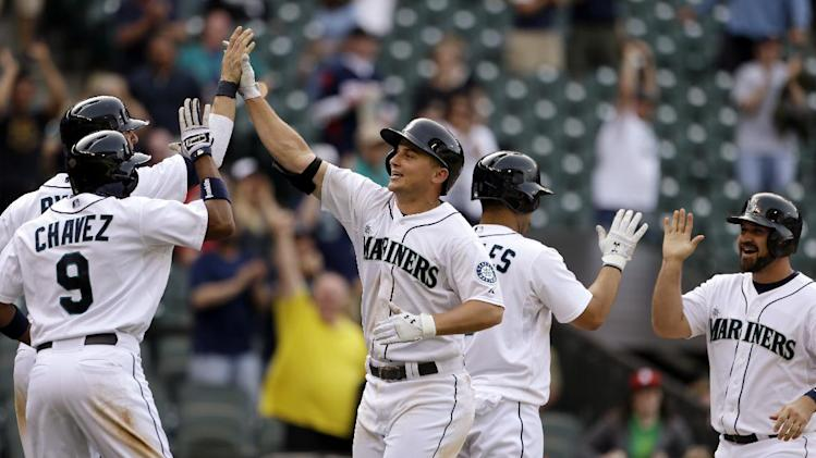 Seattle Mariners' Kyle Seager, center, is greeted at home following his grand slam against the Chicago White Sox in the 14th inning to tie a baseball game on Wednesday, June 5, 2013, in Seattle. (AP Photo/Elaine Thompson)