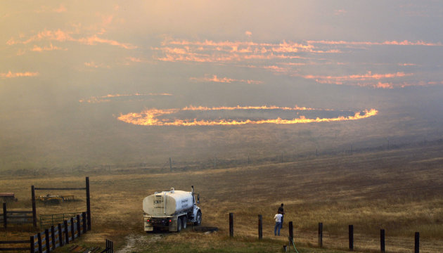 Men watch as fire roars across ranch land Tuesday, Aug. 14, 2012, on Bettas Road near Cle Elum, Wash. The fast-moving wildfire has burned 60 homes across nearly 40 square miles of central Washington g
