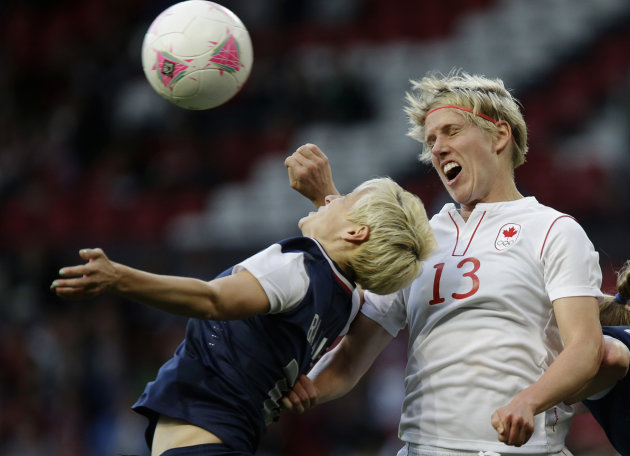 United States&#39; Megan Rapinoe, left, heads for the ball against Canada&#39;s Sophie Schmidt, right, during their semifinal women&#39;s soccer match between the USA and Canada at the 2012 London Summer Olympics, in Manchester, England, Monday, Aug. 6, 2012. (AP Photo/Hussein Malla)