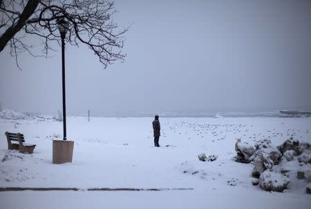A man stands in falling snow at the shore of the Hudson River in the New York City suburban town of Nyack, New York