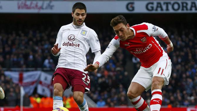 Arsenal's Ozil shoots past Aston Villa's Gil to score during their English Premier League soccer match in London