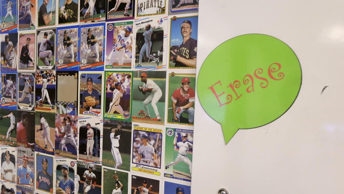 Baseball cards are shown on the wall next to a dry erase board in the Pinterest office in San Francisco, Wednesday, April 1, 2015. The San Francisco-based venture capital darling celebrated its fifth birthday in March 2015. (AP Photo/Jeff Chiu)