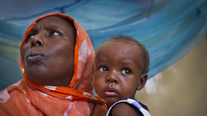 In this photo taken Wednesday, April 24, 2013, Saqa Farah, the mother of 12 children from a nomadic goat herding family in northern Somalia, holds her one-year-old baby Abdi Noor Hussein who is suffering from measles, in the isolation ward of the Benadir hospital in Mogadishu, Somalia. The international community is trying to lower the number of child deaths in Somalia with the roll-out of a new five-in-one child vaccine they say will save thousands of lives, and more regions of Somalia are at peace today than have been in 20 years, but tens of thousands of children still die every year from easily preventable diseases - in part because of resistance by al-Qaida-linked militants. (AP Photo/Ben Curtis)