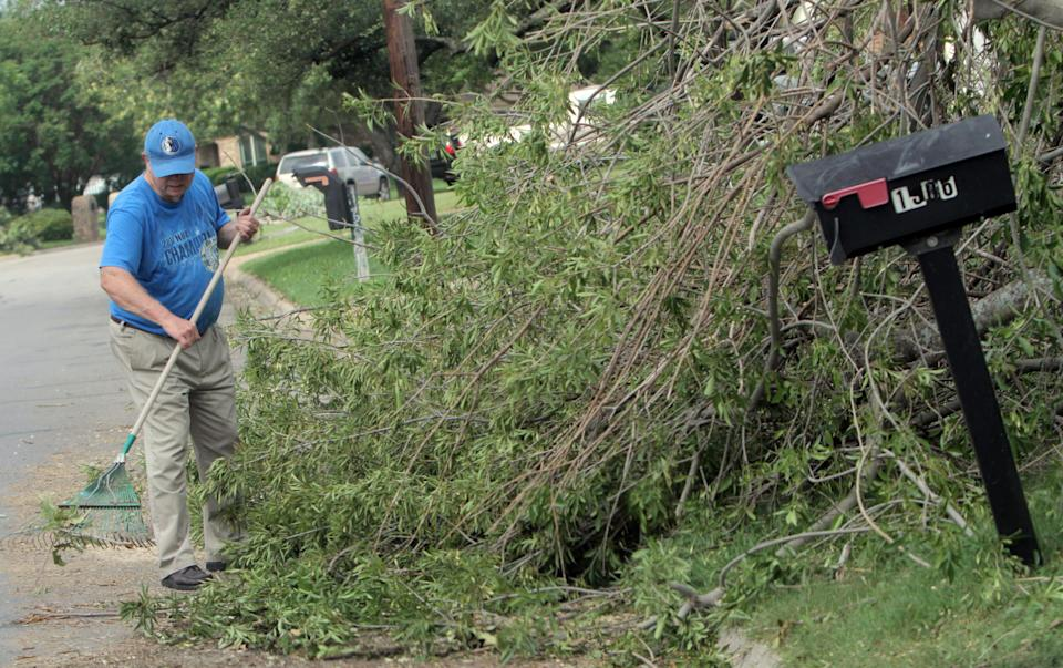 Don Graf cleans his property in Cleburne, Texas, Friday, May 17, 2013. On Wednesday, powerful storms produced 16 tornadoes in the area. (AP Photo/Mike Fuentes)