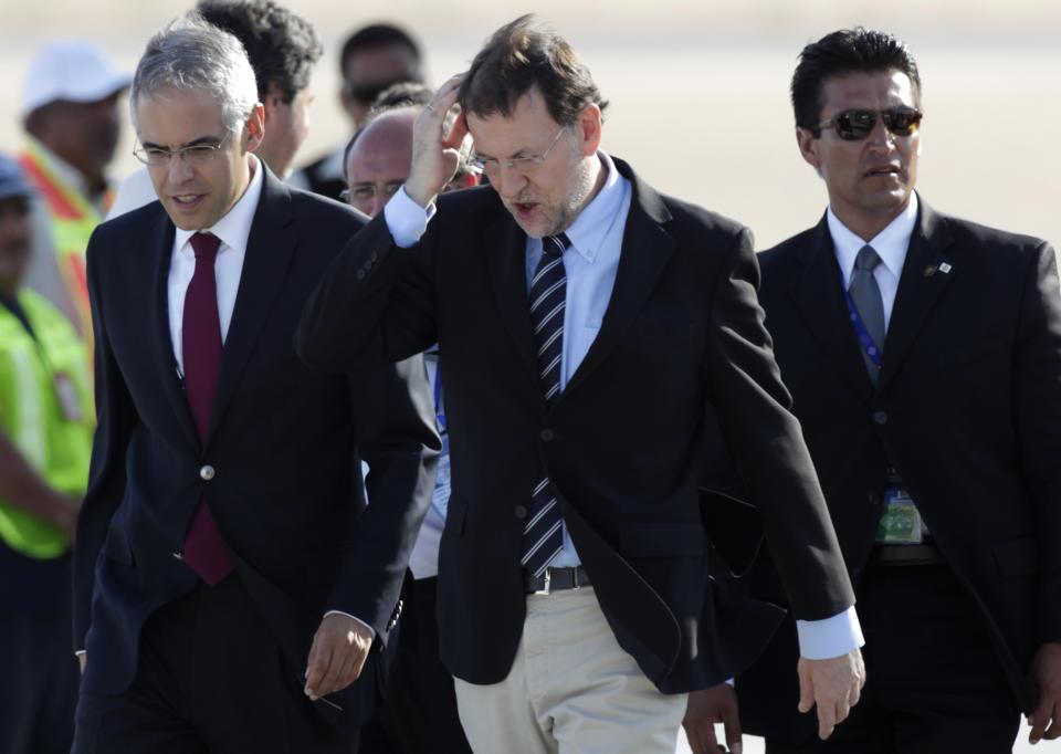 Spain's Prime Minister Mariano Rajoy, center, arrives to Los Cabos international airport to attend the G-20 Summit in Baja California Sur, Mexico, Sunday, June 17, 2012. (AP Photo/Eduardo Verdugo)