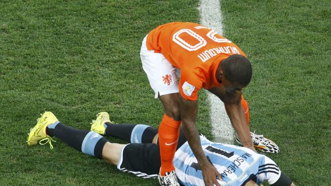 Georginio Wijnaldum of the Netherlands checks on Argentina's Javier Mascherano after colliding during their 2014 World Cup semi-finals at the Corinthians arena in Sao Paulo