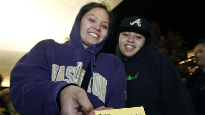 """Amanda Dollente, left, and her partner Kelly Middleton, both of Auburn, Wash., display their """"No. 1"""" ticket as first in line to be issued a marriage license to a same-sex couple, Wednesday, Dec. 5, 2012, in Seattle. King County Executive Dow Constantine was to began issuing the licenses just after midnight, Dec. 6, immediately upon certification of the November election that passed Referendum 74 allowing same-sex couples to wed. (AP Photo/Elaine Thompson)"""