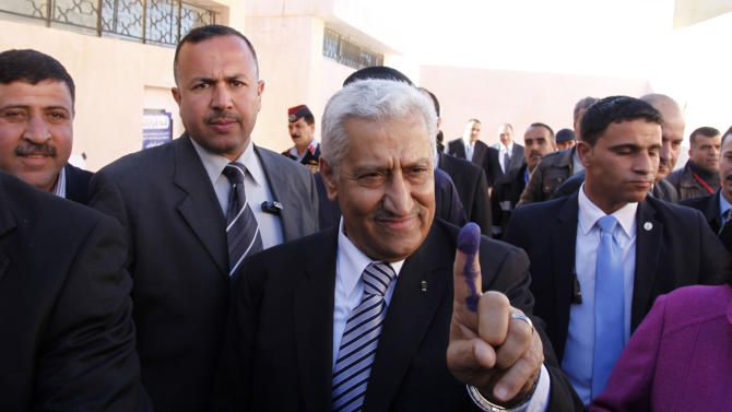 Jordanian Prime Minister Abdullah Ensour, gestures with his finger, showing the press the voting ink on his finger after he casts his vote at  a polling station during the first hours of the Jordanian Parliamentary elections, in Al-Salt, Jordan, Wednesday Jan. 23, 2013. Jordan's monarchy has touted Wednesday's parliamentary election as a watershed in the kingdom's democratization. It is the first after last year's constitutional amendments that see King Abdullah II gradually relinquishing much of his powers in running the daily affairs of the state to the legislature, although he will continue — for now — to set broader foreign and security policies. (AP Photo/Mohammad Hannon)