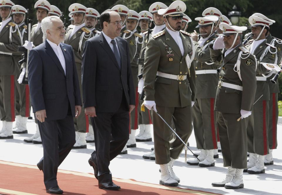 Iraqi Prime Minister Nouri al-Maliki, center, reviews an Iranian honor guard, as he is accompanied by Iranian Vice-President Mohammad Reza Rahimi, left, during an official arrival ceremony, in Tehran, Iran, Sunday, April 22, 2012. (AP Photo/Vahid Salemi)