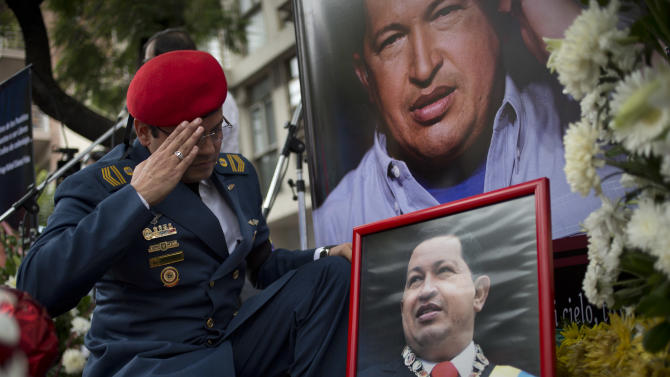A Venezuelan army officer salutes a photo of Venezuela's late President Hugo Chavez at a makeshift memorial outside the Venezuelan Embassy in Buenos Aires, Argentina on Saturday, March 9, 2013. Chavez died on March 5, 2013 after a nearly two-year bout with cancer. (AP Photo/Victor R. Caivano)
