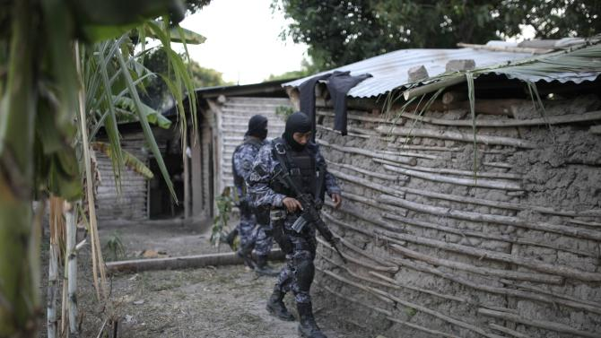 Salvadoran policemen secure a crime scene where 6 suspected members of the 18th. Street Gang  were killed at the town of Santiago Nonualco  on December 20, 2014.