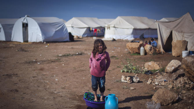 A Syrian girl who fled with her family from the violence in their village, washes clothes at a displaced camp, in the Syrian village of Atma, near the Turkish border with Syria. Wednesday, Nov. 7, 2012. (AP Photo/ Khalil Hamra)