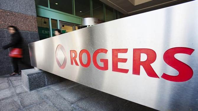 A woman walks by a sign at the Rogers Communications headquarters building on the day of their annual general meeting for shareholders in Toronto