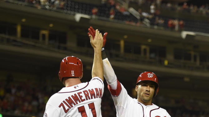 Washington Nationals' Ian Desmond (20) celebrates his two-run home run during the eighth inning of a baseball game against the Miami Marlins with Ryan Zimmerman (11), Monday, May 4, 2015, in Washington. The Nationals won 6-4. (AP Photo/Nick Wass)
