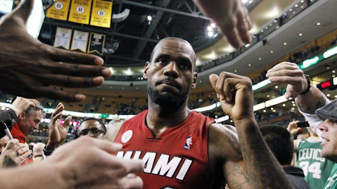 Miami Heat's LeBron James (6) celebrates with fans as he walks off the court after their NBA basketball game against the Boston Celtics in Boston, Monday, March 18, 2013. James made the go-ahead jumper with 10.5 seconds left to lead Miami to its 23rd consecutive victory, 105-103 over the Celtics. (AP Photo/Michael Dwyer)