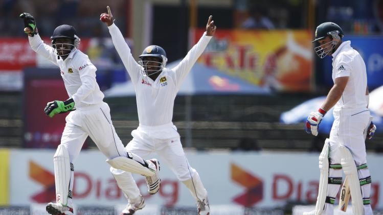 Sri Lanka's wicketkeeper Dickwella and Silva celebrate the dismissal of South Africa's Elgar during the second day of their second test cricket match in Colombo