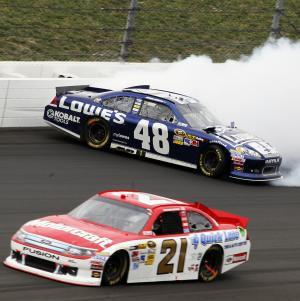 Trevor Bayne (21) passes Jimmie Johnson (48) as Johnson hits the wall during a NASCAR Sprint Cup Series auto race at Kansas Speedway in Kansas City, Kan., Sunday, Oct. 21, 2012. (AP Photo/Colin E. Braley)