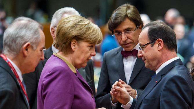 German Chancellor Angela Merkel, second left, speaks with French President Francois Hollande during a round table meeting at an EU summit in Brussels on Friday, March 15, 2013. On the second anniversary of an uprising that evolved into Syria's brutal civil war, the European Union's national leaders will likely discuss whether to arm rebels trying to overthrow the regime of Bashar Assad. (AP Photo/Geert Vanden Wijngaert)