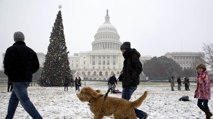 People walk in light snow flurries at the U.S. Capitol in Washington