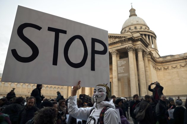 A protestor holds a poster asking for the end of violence in Syria during a demonstration in front of the Pantheon in Paris