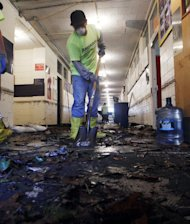 Workers scrape up mud and tiles from flood-damaged Saint Rose High School in Belmar, N.J., Sunday, Nov. 4, 2012, as the region tries clean up the damage from Monday's storm surge by Superstorm Sandy. (AP Photo/Mel Evans)