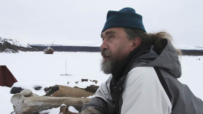 In this photo taken Oct. 23, 2010 Russian scientist Sergey Zimov talks about mammoth bones he has collected in this remote area of northeast Siberia. Zimov has stacked the bones on a barge in the river near the Northeast Science Station, which he directs, in the town of Chersky, Russia. Zimov believes mammoths, woolly rhinos and other Ice Age animals became extinct after human hunters killed too many to maintain the delicate balance between the animals and the grasslands that fed them. (AP Photo/Arthur Max)