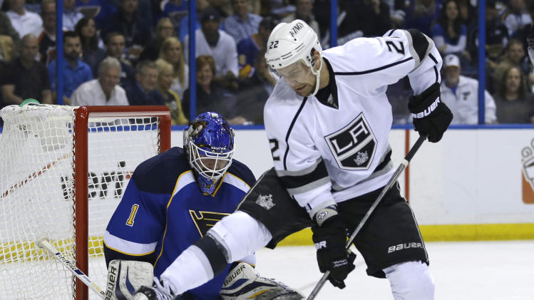 St. Louis Blues goalie Brian Elliott, left, watches the puck as it goes between the legs of Los Angeles Kings' Trevor Lewis during the first period in Game 5 of a first-round NHL hockey Stanley Cup playoff series, Wednesday, May 8, 2013, in St. Louis. (AP Photo/Jeff Roberson)