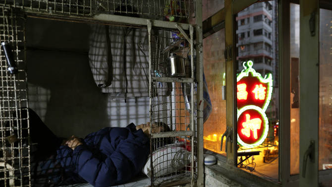 In this Jan. 25, 2013 photo, 62-year-old Cheng Man Wai lays in his cage, measuring 1.5 square meters (16 square feet),  which he calls home, in Hong Kong. For many of the richest people in Hong Kong, one of Asia's wealthiest cities, home is a mansion with an expansive view from the heights of Victoria Peak. For some of the poorest, home is a metal cage. Some 100,000 people in the former British colony live in what's known as inadequate housing, according to the Society for Community Organization, a social welfare group.   (AP Photo/Vincent Yu)