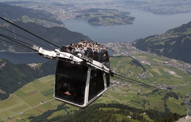 "People ride on the inauguration trip of the world's first open-air double-decker cable car system, the newly-built ""Cabrio"", on the Stanserhorn Mountain, near Lucerne."