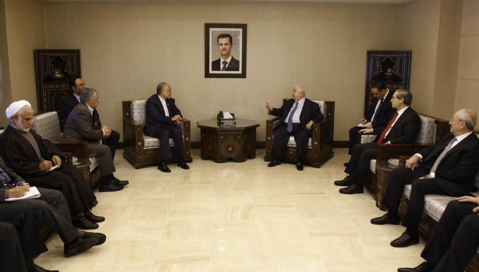Iranian Foreign Minister Ali Akbar Salehi, center left, meets with Syrian Foreign Minister Walid Moallem, center right, in Damascus, Syria, Wednesday, Sept. 19, 2012. The portrait of Syrian President Bashar Assad is seen top center.(AP Photo/Muzaffar Salman)