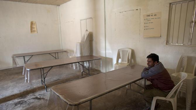In this Feb. 11, 2014 photo, a man sits in a community kitchen dining area in Cochoapa El Grande, Mexico. The kitchen is supposed to open from Monday to Friday and provide free food for breakfast and lunch, but on this day no food was being prepared. (AP Photo/Dario Lopez-Mills)