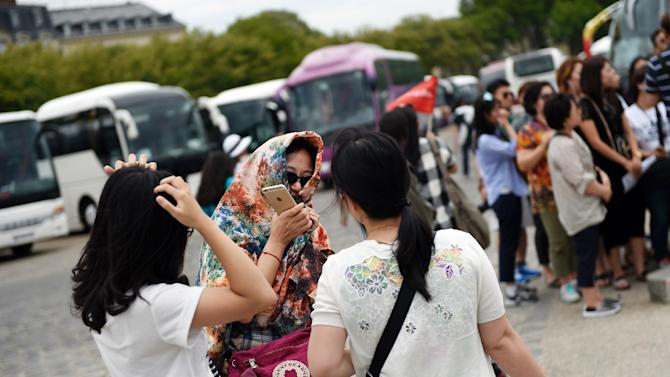 Chinese tourists wait for their bus after visiting the Palace of Versailles, outside Paris