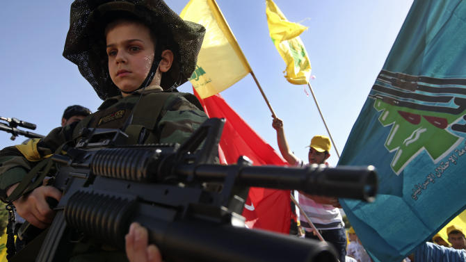 """A Lebanese boy wearing a military uniform and holding a toy rifle  attends a rally commemorating """"Liberation Day,"""" which marks the withdrawal of the Israeli army from southern Lebanon in 2000, in Mashghara village, Bekaa valley, Lebanon, Saturday May 25, 2013. Nasrallah says his Shiite militant group will not stand idly by while its chief ally Syria is under attack. Nasrallah says Hezbollah members are fighting in Syria against Islamic extremists who pose a danger to Lebanon, publicly confirming for the first time that his men were fighting in Syria. (AP Photo/Hussein Malla)"""