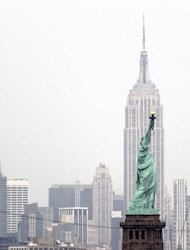 FILE - This May 8, 2012 file photo shows the New York's Empire State Building behind the The Statue of Liberty from Bayonne, N.J. (AP Photo/Julio Cortez, file)