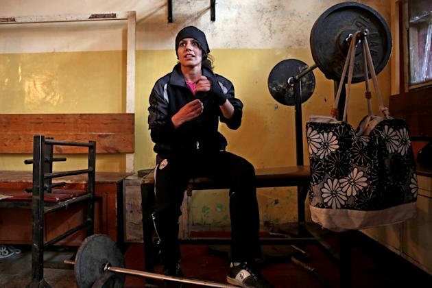In this Wednesday, March, 5, 2014 photo, an Afghan female boxer prepares for practice at the Kabul Stadium boxing club. The Afghanistan National Olympic Committee boxing club has fewer than a dozen wo
