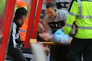 John Fleck, bottom, receives treatment on the head injury he suffered on Saturday