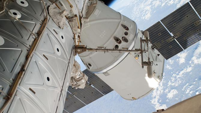 FILE - This April 22, 2014 file photo provided by NASA shows a photo of the SpaceX Dragon spacecraft docked to the International Space Station and was photographed by one of two spacewalking astronauts. On Sunday, May 18, 2014, after a one-month visit, the SpaceX cargo ship was for return to Earth. The astronauts released it using the International Space Station's big robot arm. (AP Photo/NASA, File)