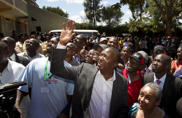 Kenyan Presidential candidate Uhuru Kenyatta waves to queuing voters after casting his vote, accompanied by his wife Margaret Wanjiru Gakuo, below right, at the Mutomo primary school near Gatundu, nor