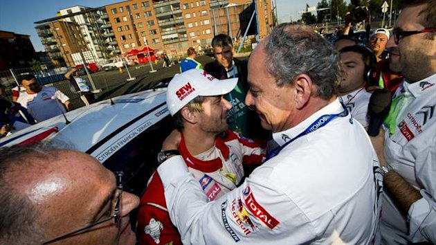 Sebastien Loeb is congratulated by Citroen's General Manager Frederic Banzet