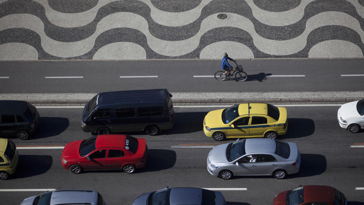 """A man pedals his bike past cars stopped in traffic at Copacabana in Rio de Janeiro, Brazil, Thursday, May 10, 2012. The upcoming Rio + 20 conference, billed as a """"historic opportunity"""" to build a greener future, appears to be going up in smoke. President Barack Obama won't be there, and the leaders of Britain and Germany have bowed out. Entire delegations have canceled. The conference is the follow-up to the U.N.'s 1992 Earth Summit, also held in Rio, which helped put climate change on the world agenda. (AP Photo/Felipe Dana)"""