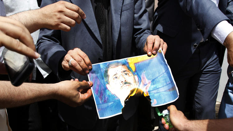 Iraqi protesters burn a poster depicting Egyptian President Mohammed Morsi and chant against the Muslim Brotherhood and the president during a protest in front of the Egyptian consulate in Basra, 340 miles (550 kilometers) southeast of Baghdad, Iraq, Friday, June 28, 2013. (AP Photo/Nabil al-Jurani)