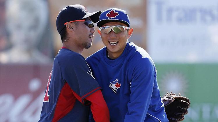 Boston Red Sox pitcher Shunsuke Watanabe, left, and Toronto Blue Jays third baseman Muneniori Kawasaki embrace before a spring training baseball game in Dunedin, Fla., Friday, March 14, 2014