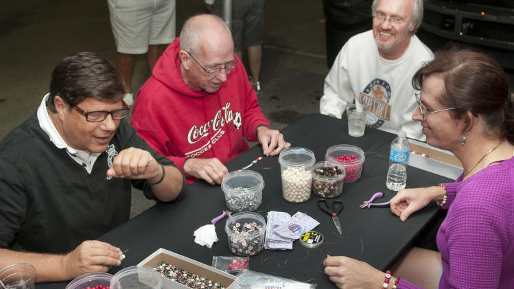 Participants, including, Bob Rose, 2nd from left, make items from beads at the Wilton Manors Out of the Closet (OTC) Block Party & Insti-Test Launch Marking the 5th anniversary of Wilton Manors OTC in Wilton Manors, Florida on Saturday, February 2nd, 2013 at the Hagan Park/City Hall parking lot in Wilton Manors, FL. (Mitchell Zachs /AP Images for AIDS Healthcare Foundation)