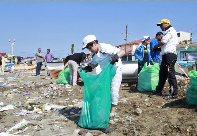 A volunteer picks up rubbish along Tamenfoust beach, 20 km east of Algiers