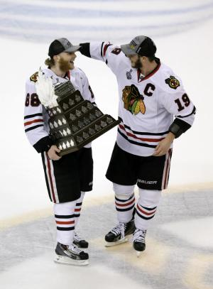 Chicago Blackhawks right wing Patrick Kane, left, is congratulated by Chicago Blackhawks center Jonathan Toews, right, as Kane carries the Conn Smythe trophy, awarded to the team's most valuable player, after the Blackhawks beat the Boston Bruins 3-2 in Game 6 of the NHL hockey Stanley Cup Finals Monday, June 24, 2013, in Boston. (AP Photo/Charles Krupa)