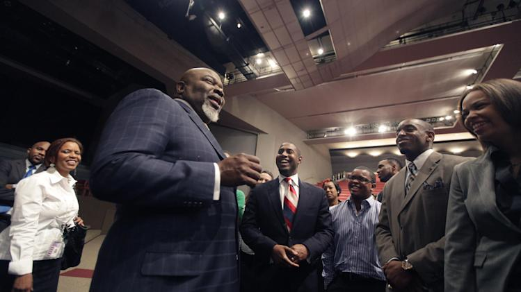 This Aug. 13, 2012 photo shows Bishop T.D. Jakes, foreground, chatting with a group of young adults he mentors at the Potters House in Dallas. Bishop Jakes work as a film producer has motivated him to mentor more young people.  As producer for the remake of Sparkle staring Whitney Houston, Jakes and others see Houston's spirit of mentoring  and true-to-life role in the film, in which she plays a singer trying to raise her children in the church so they avoid some of the mistakes she made during her career. (AP Photo/LM Otero)